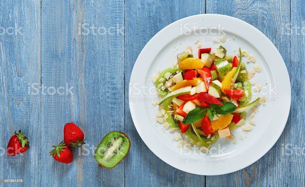 Vegan food. Vegetarian diet. Fruit salad at white plate. Fruit salad...
