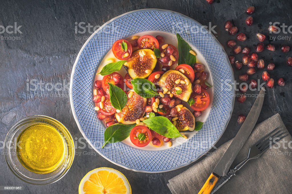 Fruit salad with fig and cherry tomatoes on ceramic plate stock photo