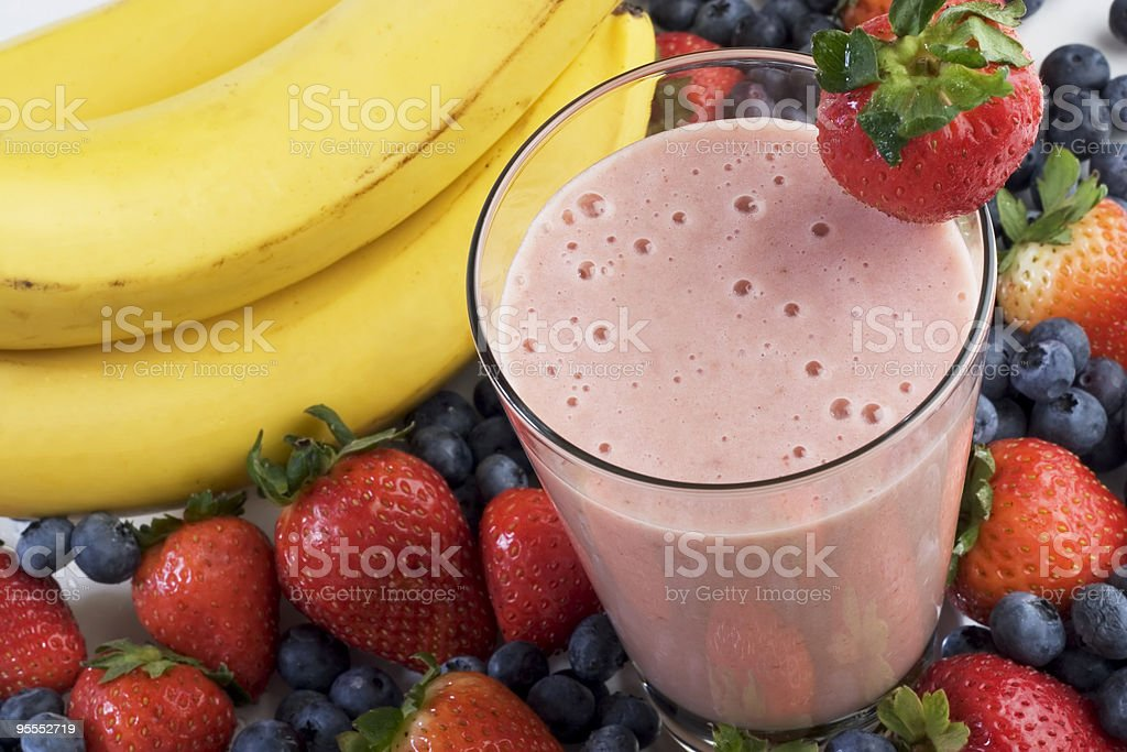 A fruit smoothie surrounded by berries and bananas stock photo