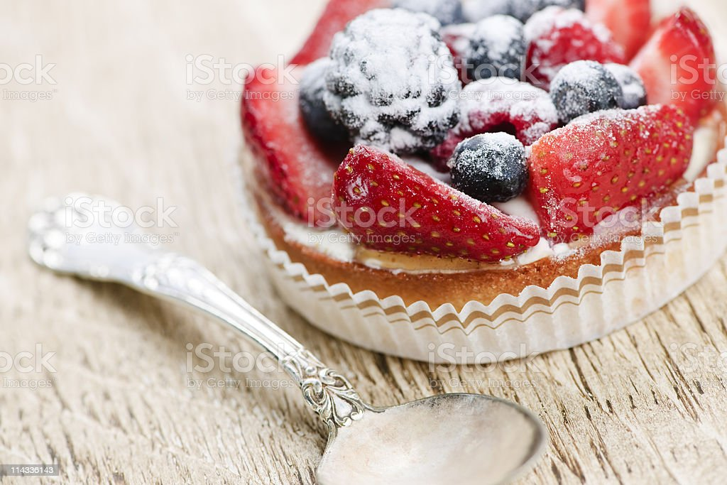 Fruit tart ready to eat near a silver spoon royalty-free stock photo