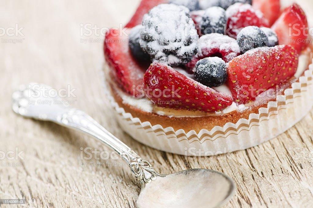 Fruit tart ready to eat near a silver spoon stock photo