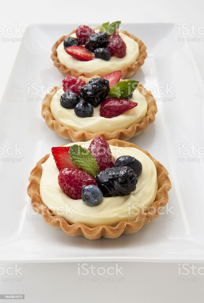 Fruit Tarts On a Serving Platter on a Light Background. stock photo