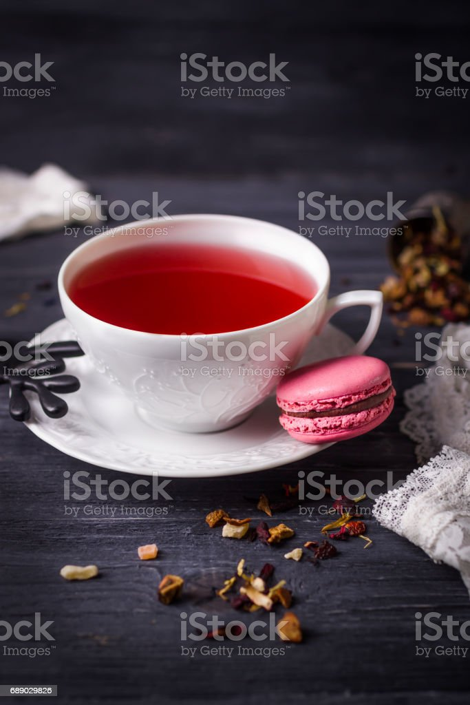 Fruit tea and pink raspberry macaron on black wooden background. Traditional French sweets stock photo