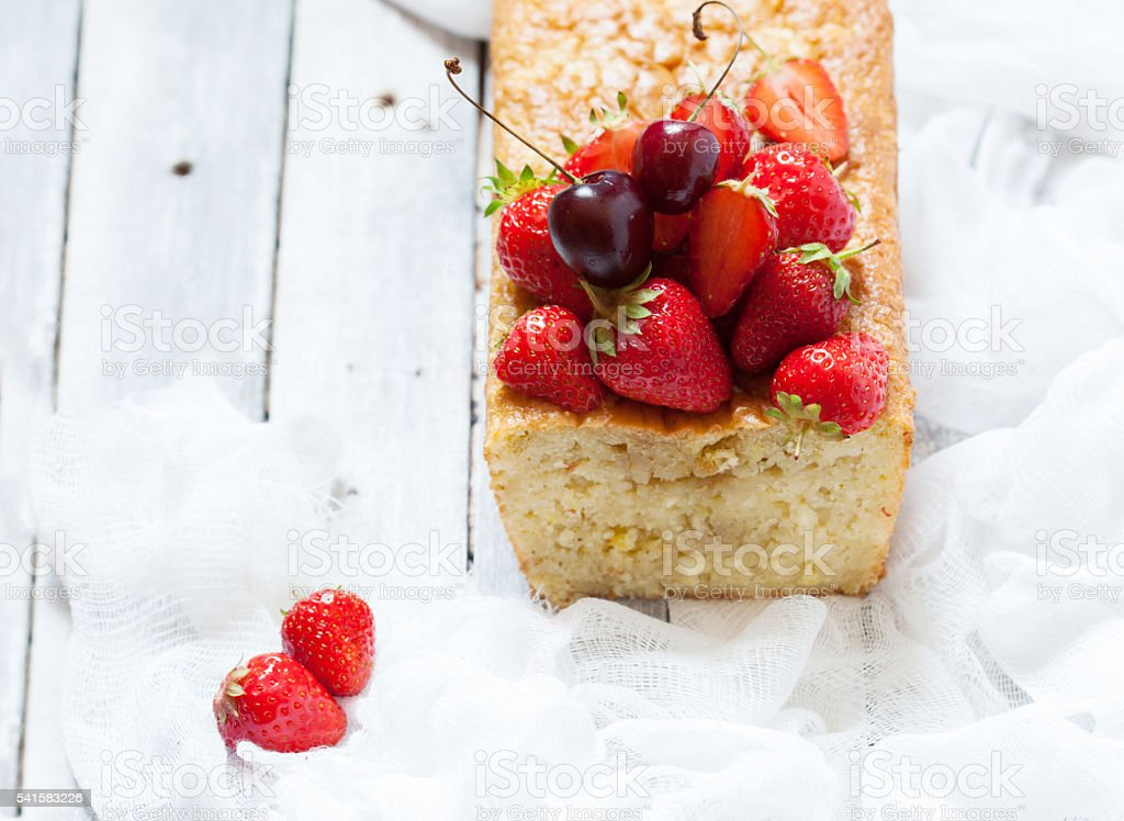 Fruitcake with strawberry and cherry topping stock photo