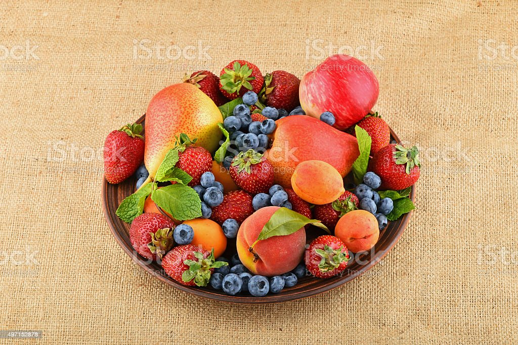Fruits and berries mix in ceramic plate on burlap canvas royalty-free stock photo