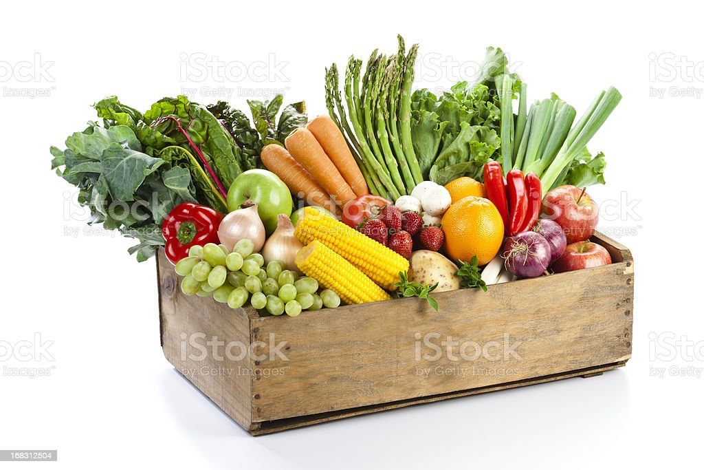 Fruits and vegetables in woodden crate isolated on white backdrop stock photo