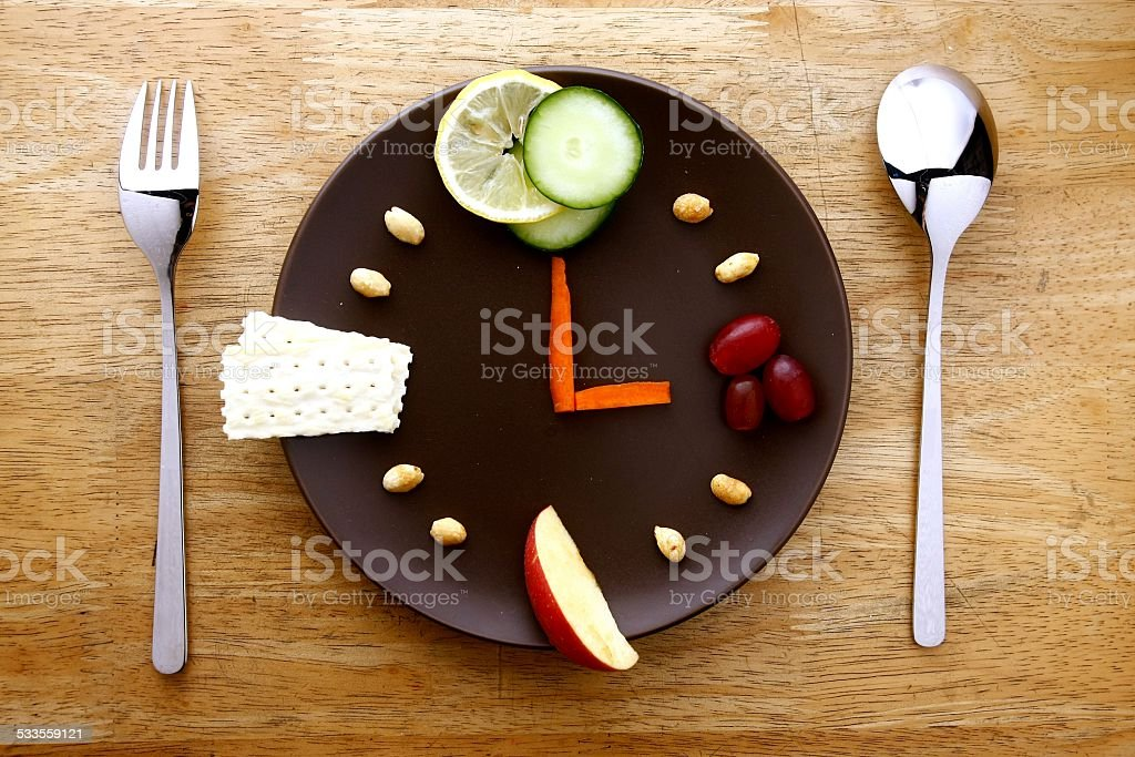 Fruits and vegetables on a plate arranged like a clock stock photo