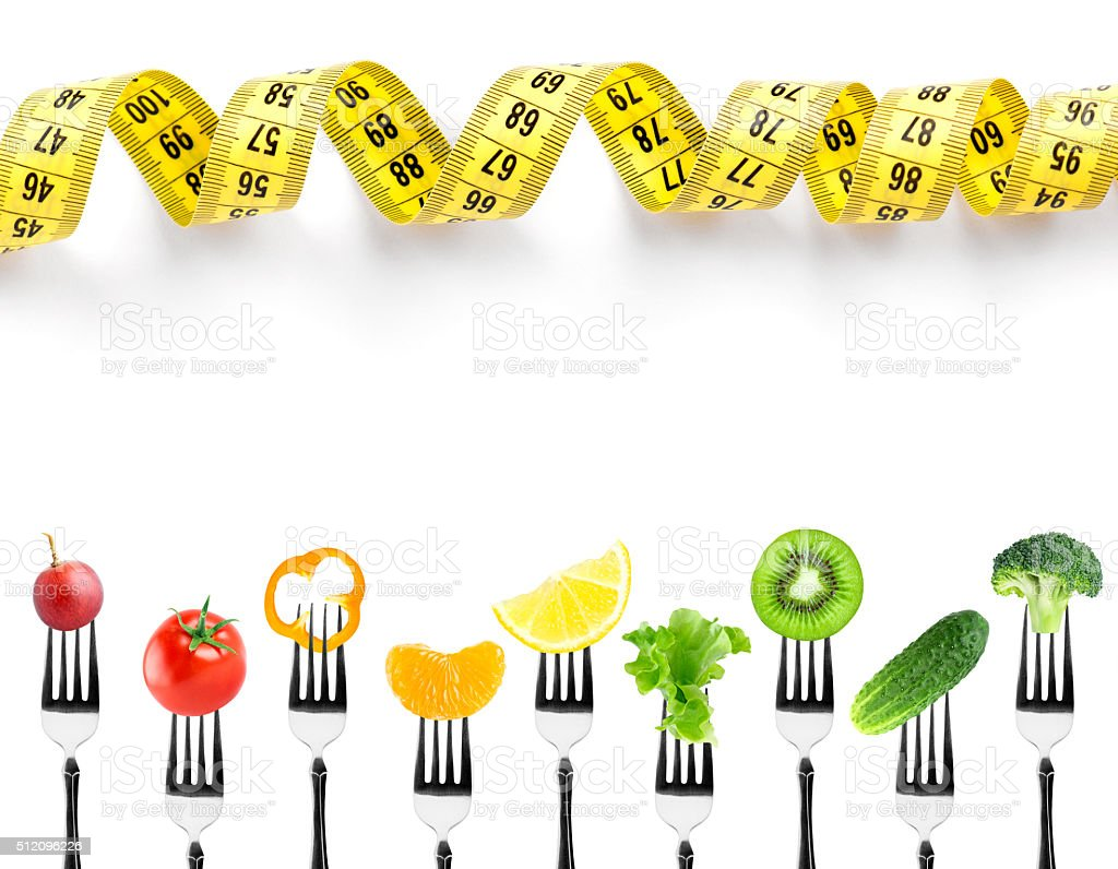 Fruits and vegetables on fork with measuring tape stock photo