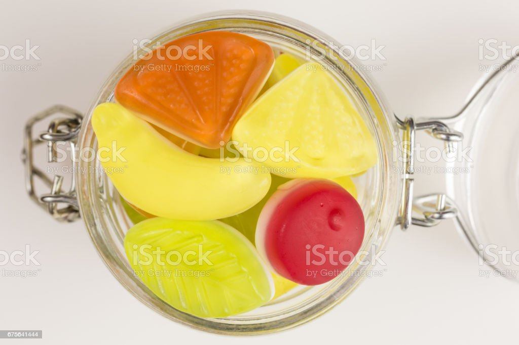 fruity yogurt gummy candies in glass jar stock photo
