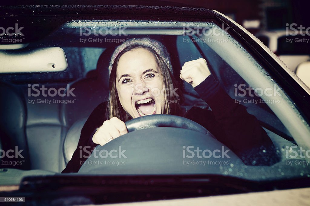 Frustrated and furious woman driver shakes fist through windshield stock photo