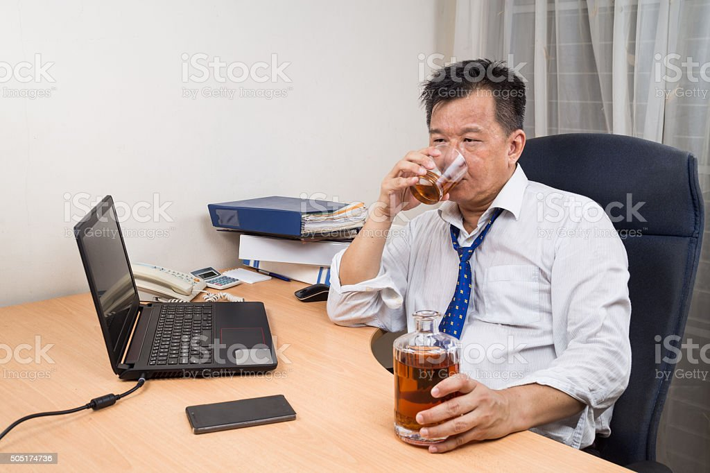 Frustrated and stressful Asian manager drinking hard liquor in o stock photo