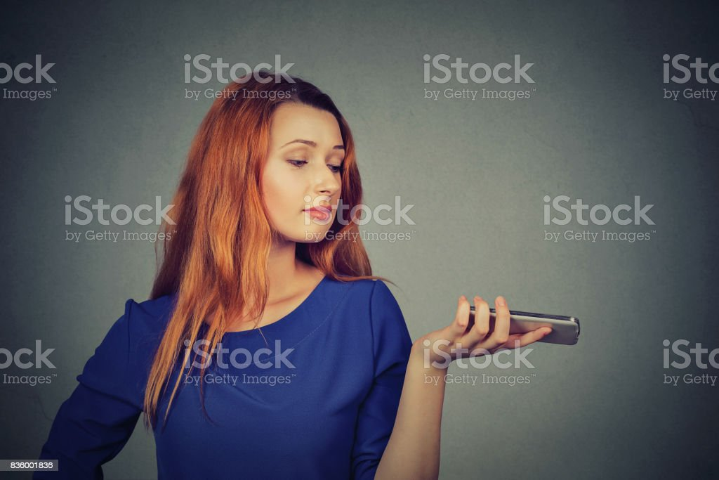 Frustrated annoyed upset woman with mobile phone standing by gray wall background stock photo