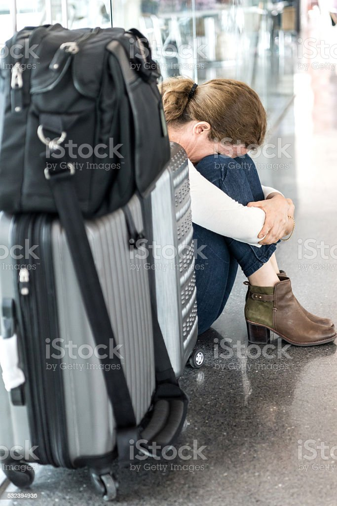 Frustrated Business woman sitting at the airport terminal floor stock photo