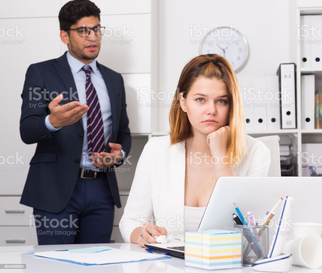 Frustrated business woman with angry chief stock photo