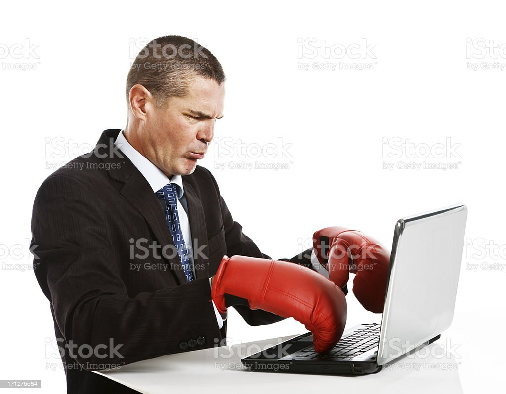 Frustrated businessman clumsily trying to type in boxing gloves royalty-free stock photo