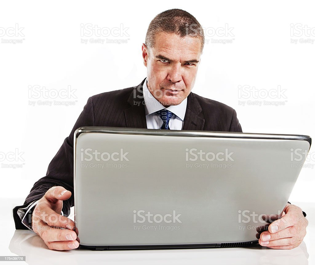 Frustrated businessman frowns behind laptop royalty-free stock photo