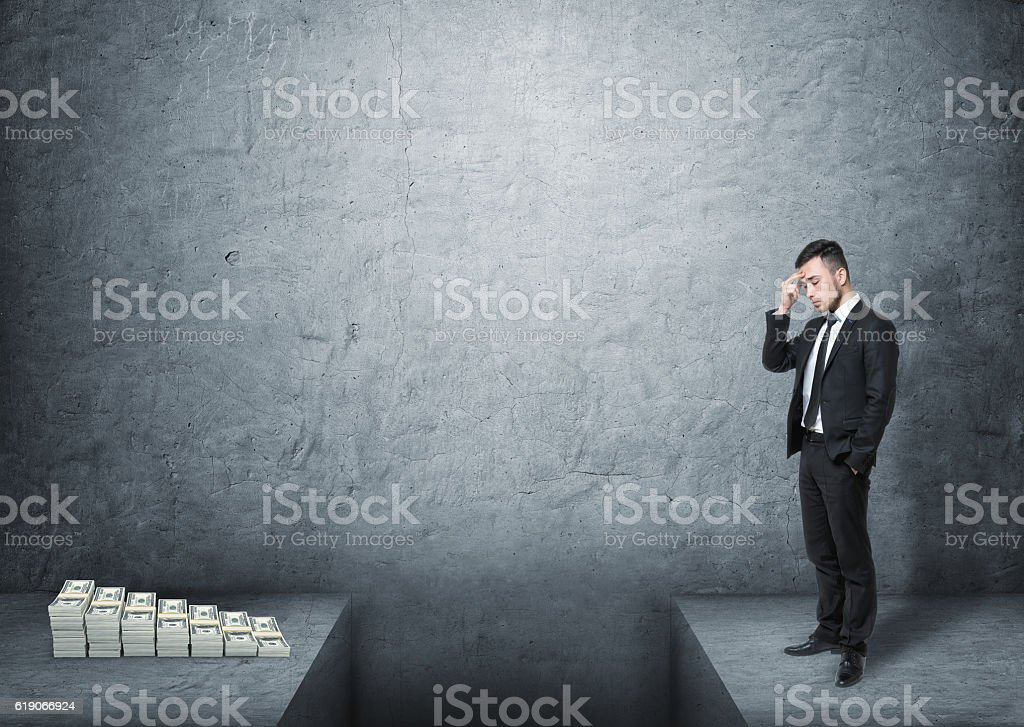 Frustrated businessman full-height standing in front of money with stock photo