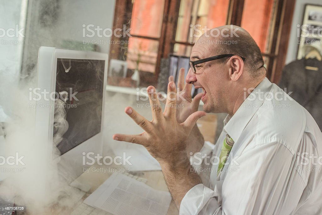 Frustrated businessman looking at computer screen stock photo
