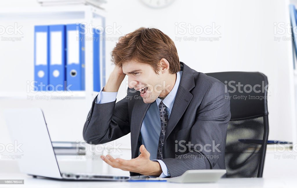 Frustrated businessman on a laptop at work in an office stock photo
