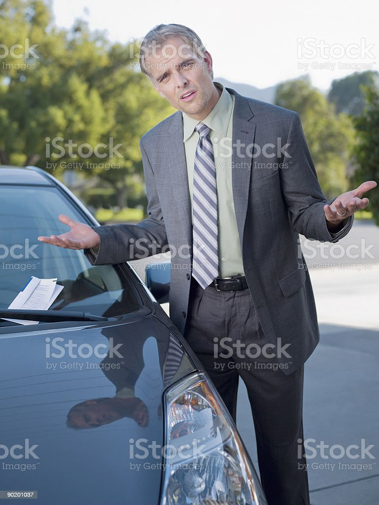 Frustrated businessman shrugging at parking ticket on windshield stock photo