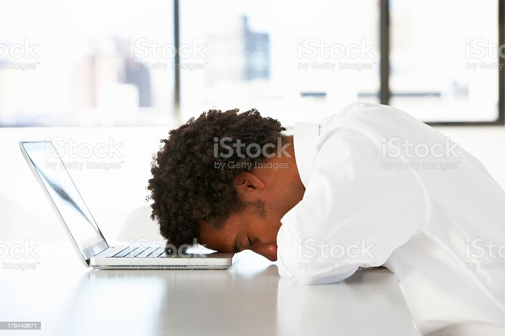Frustrated Businessman Sitting At Desk In Office Using Laptop stock photo