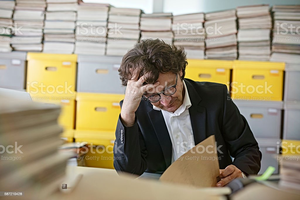 Frustrated businessman sitting at desk Overloaded With Paperwork stock photo