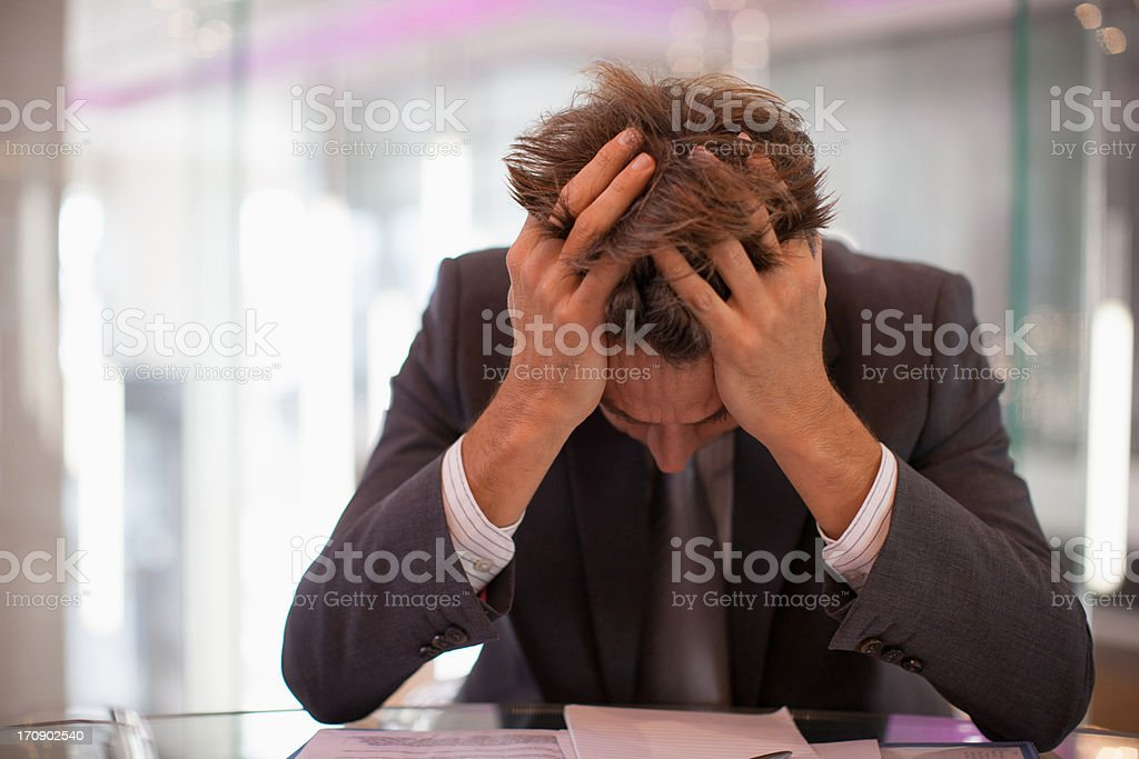 Frustrated businessman sitting at desk with  head in hands stock photo