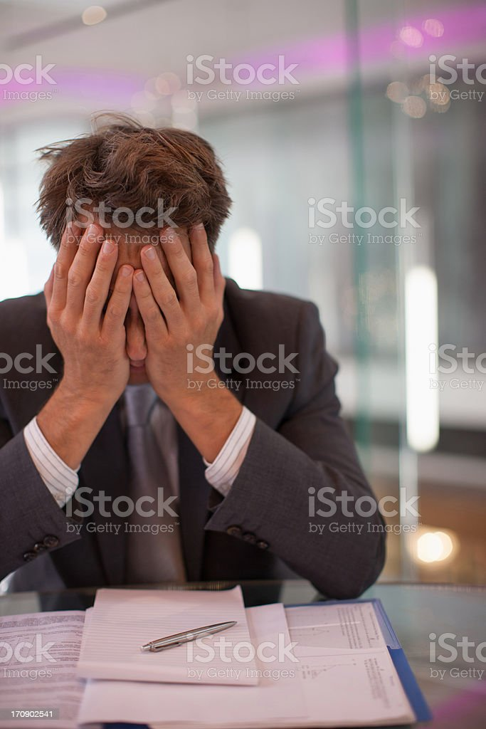 Frustrated businessman sitting at desk with  head in hands royalty-free stock photo