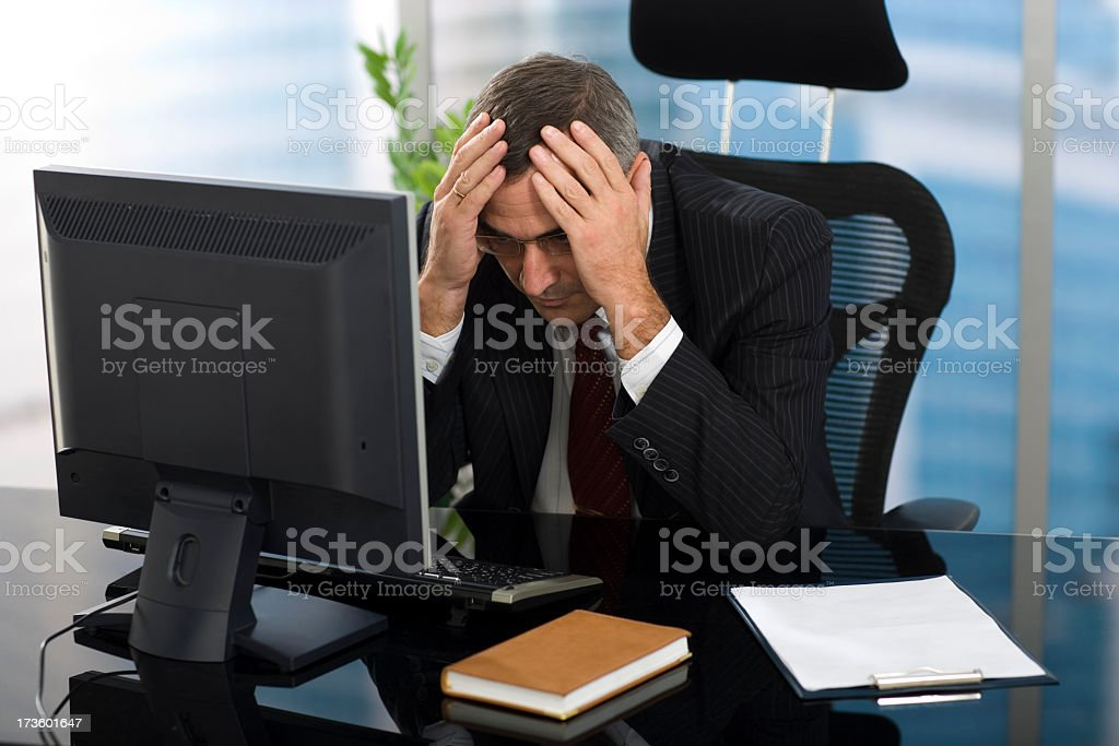 A frustrated businessman sitting at his computer royalty-free stock photo