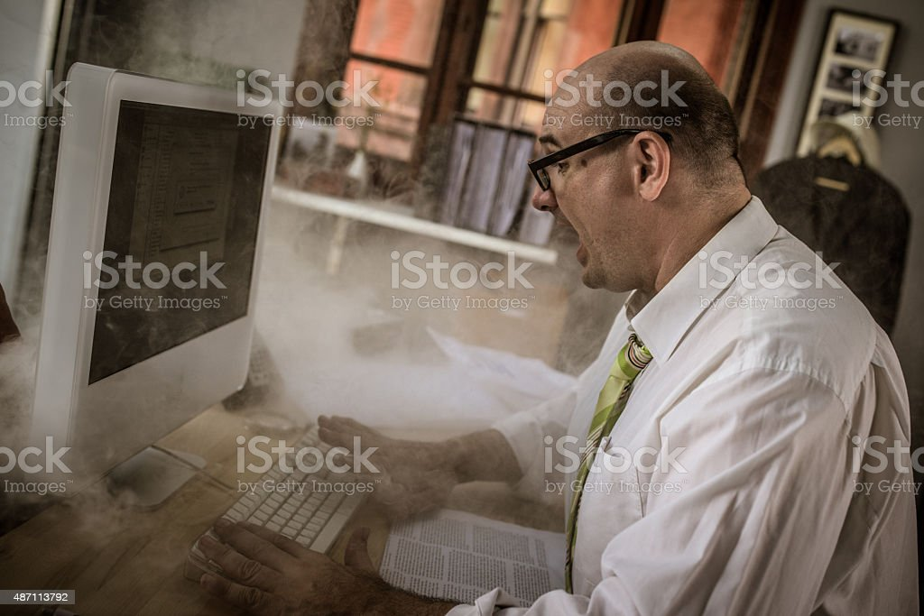 Frustrated businessman using computer stock photo