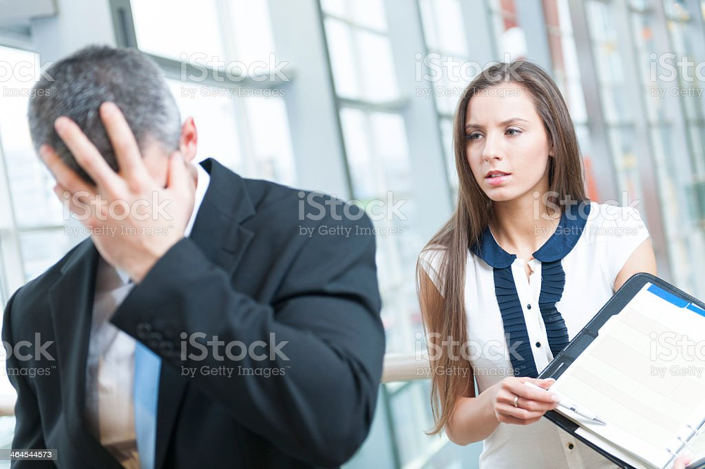 A frustrated businessman walks away from a coworker stock photo