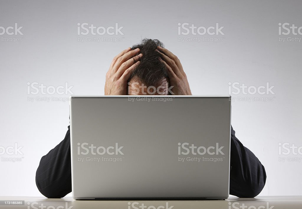 Frustrated businessman with his head in his hands behind laptop royalty-free stock photo