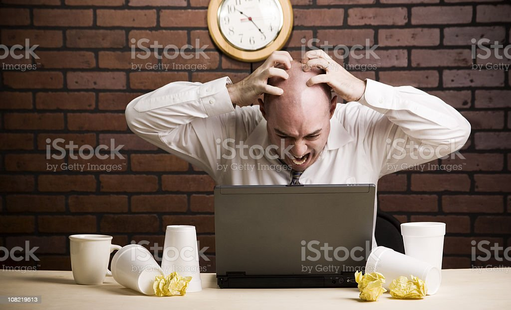 Frustrated Businessman Working on Laptop and Drinking Coffee stock photo