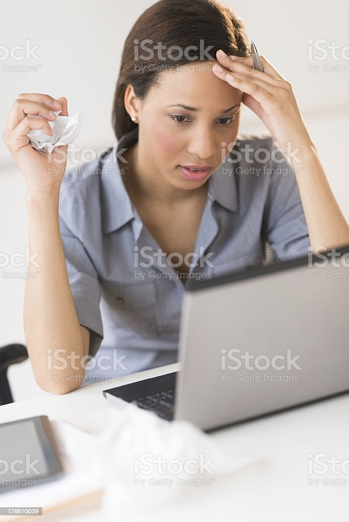 Frustrated Businesswoman Looking At Laptop While Sitting In Office royalty-free stock photo