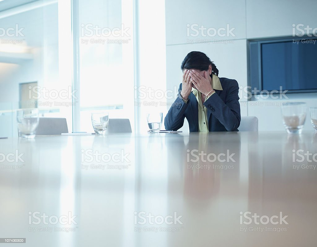 Frustrated businesswoman sitting at conference table royalty-free stock photo