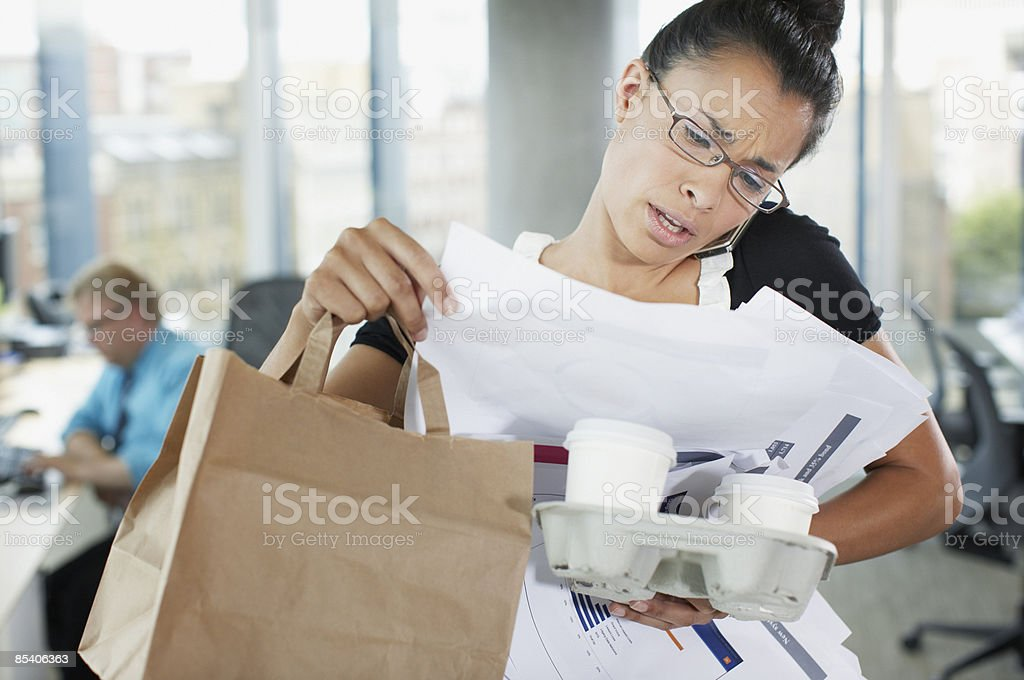Frustrated businesswoman talking on cell phone with paperwork and coffee stock photo