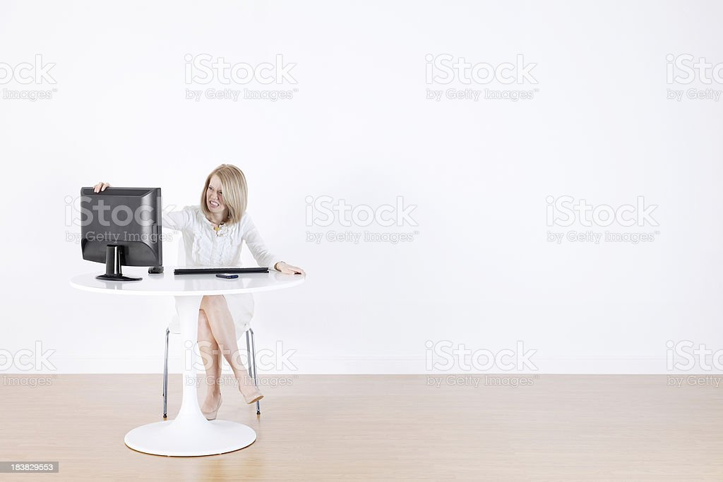 Frustrated businesswoman with computer at desk stock photo
