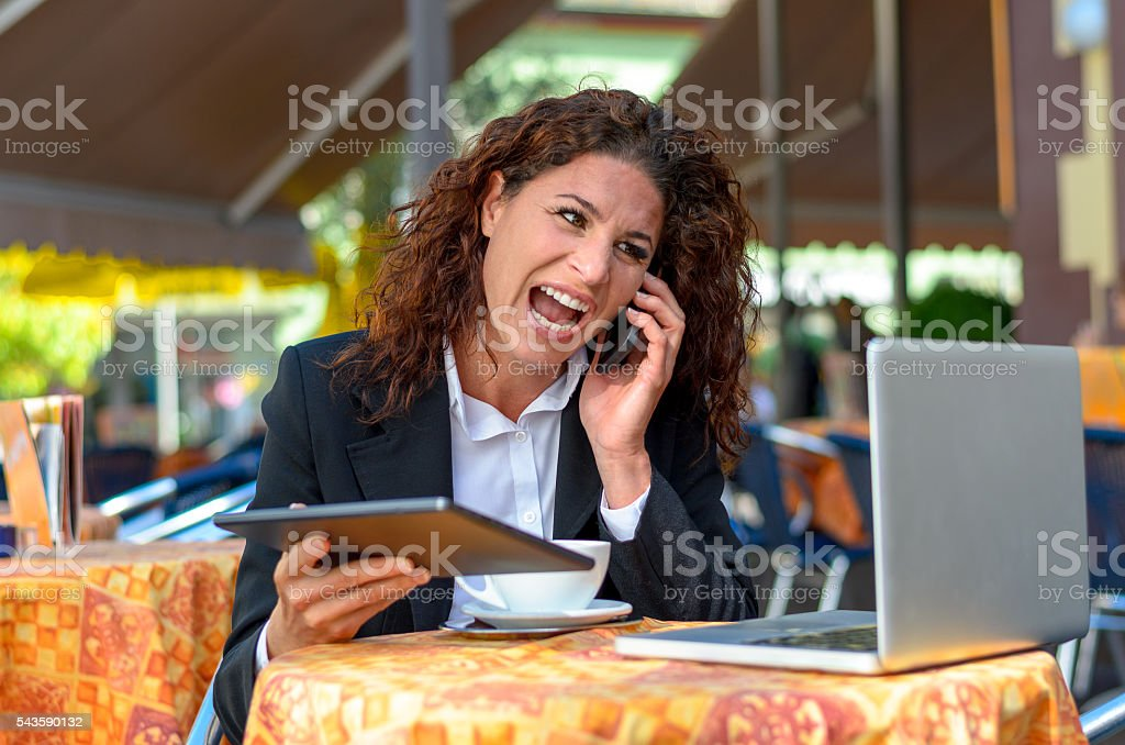 Frustrated businesswoman yelling into her mobile stock photo