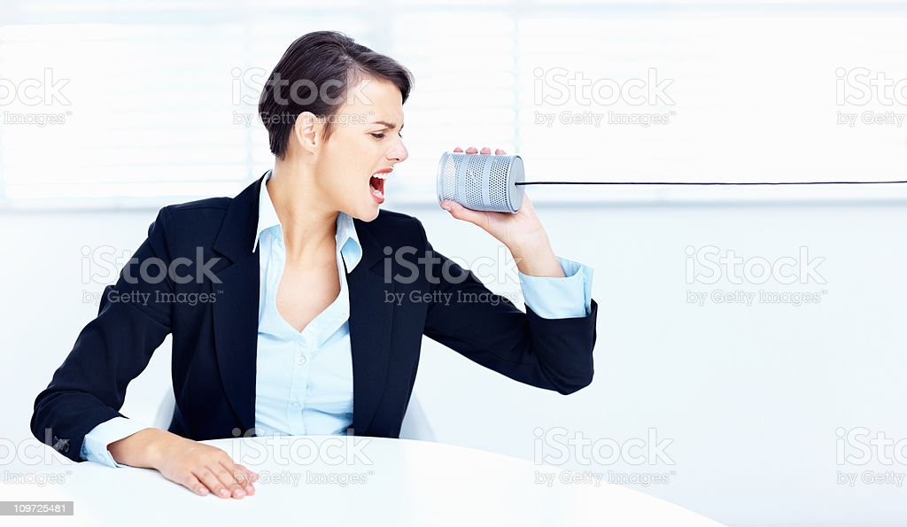 Frustrated Caucasian woman screaming into a tin can phone royalty-free stock photo
