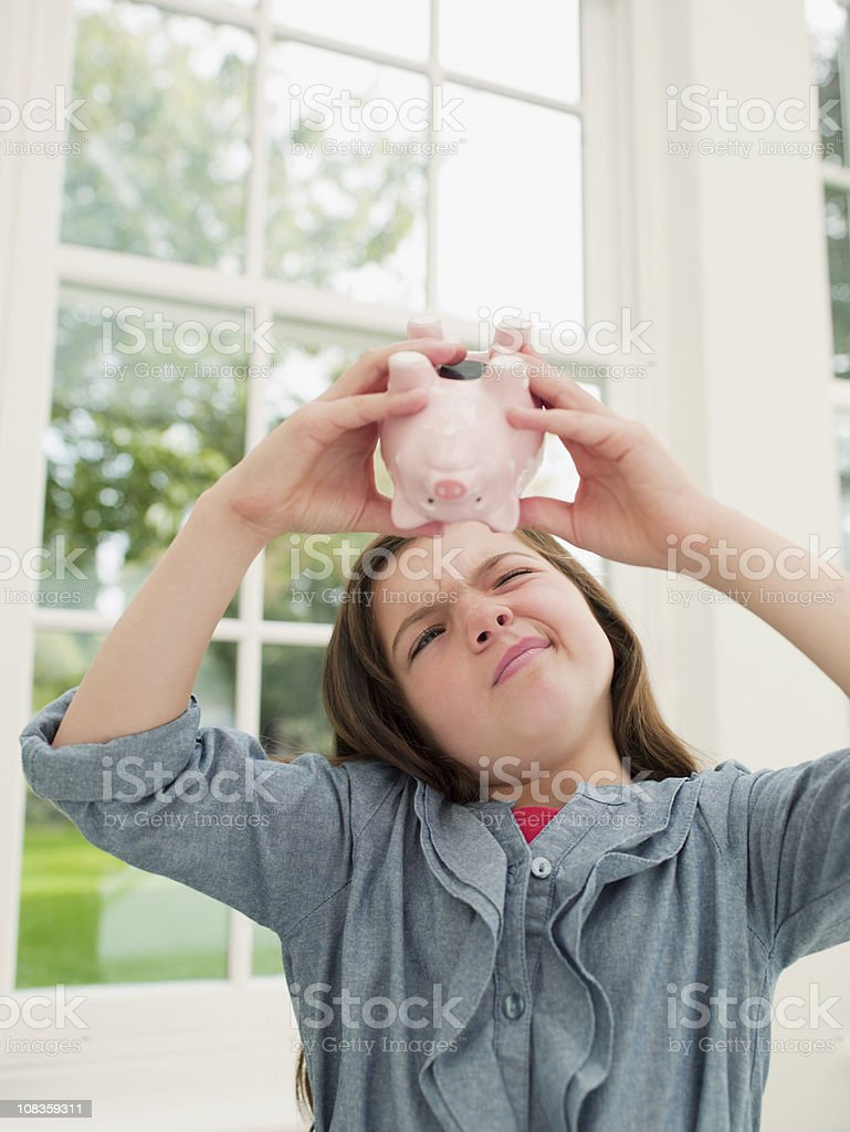 Frustrated girl emptying piggy bank royalty-free stock photo