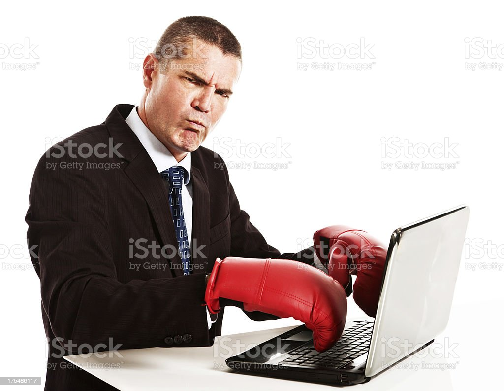 Frustrated grumpy businessman in boxing gloves cannot type on laptop stock photo