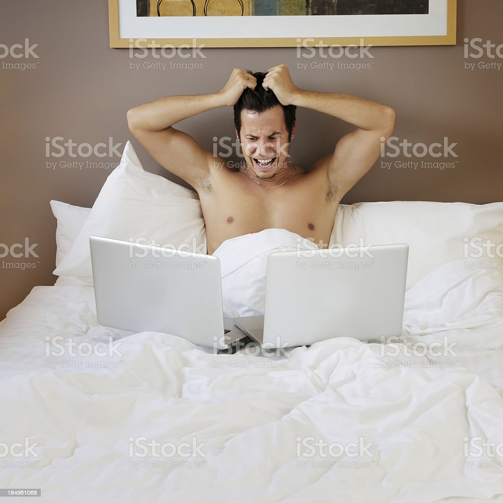 Frustrated Guy with Laptop in Bed royalty-free stock photo