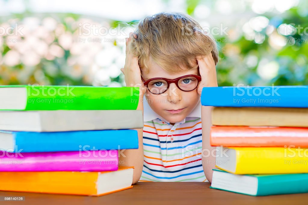 frustrated little schoolboy with glasses and books stock photo