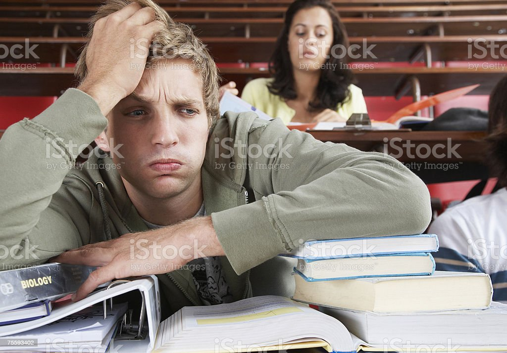 A frustrated male in a classroom with two students in background royalty-free stock photo