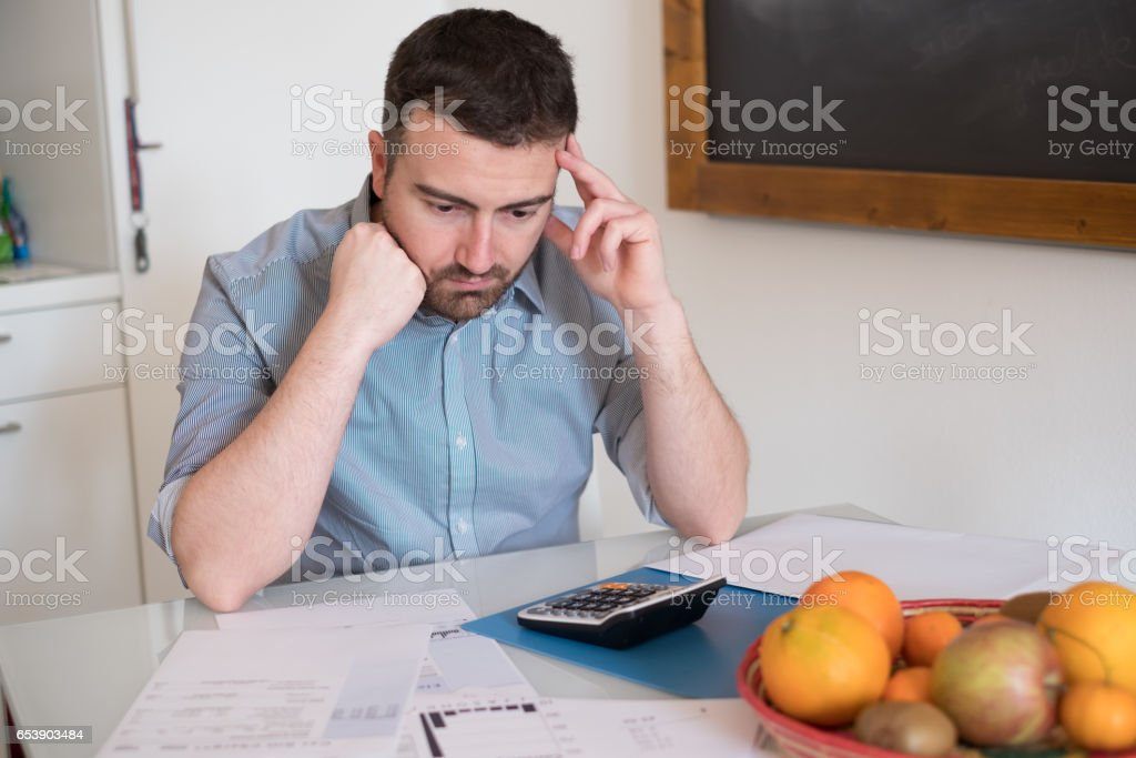 Frustrated man calculating bills and taxes stock photo