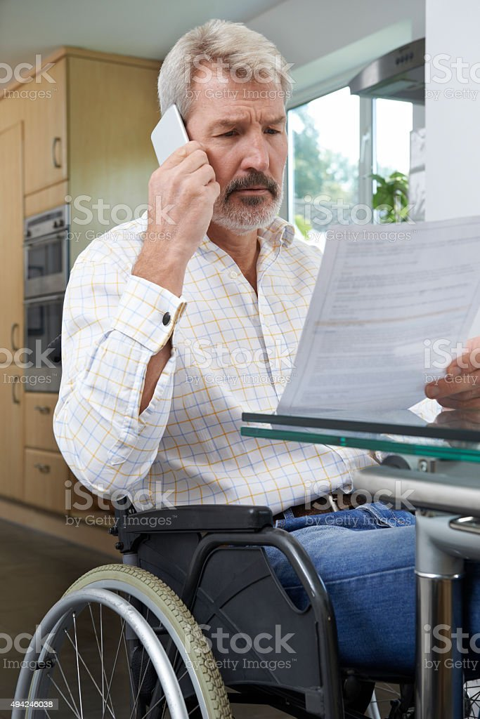 Frustrated Man In Wheelchair Making Phone Call Whilst Reading Le stock photo