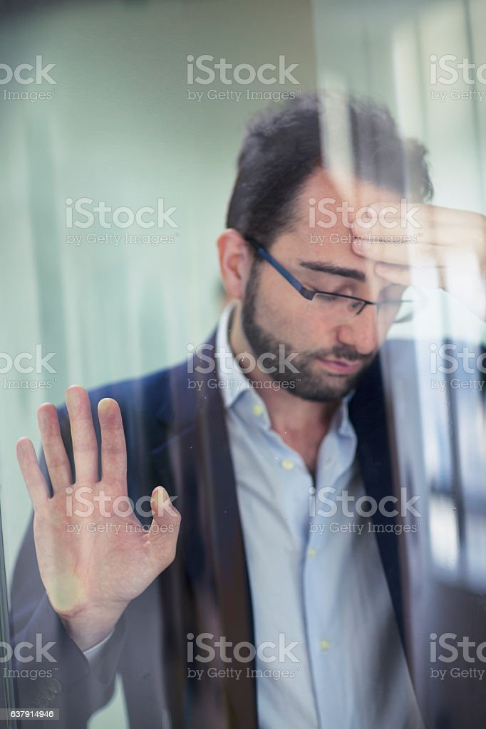 Frustrated man leaning against glass wall stock photo