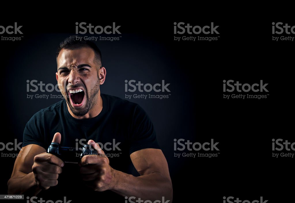 Frustrated man playing video games against dark background stock photo