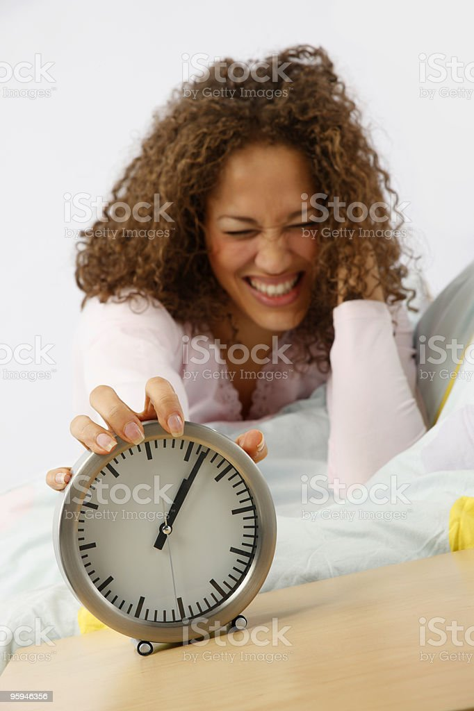 frustrated mixed-race woman in bed switching noisey alarm clock off royalty-free stock photo