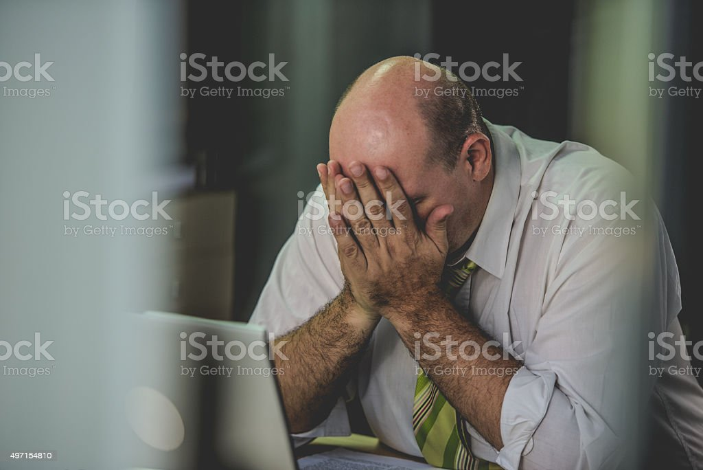 Frustrated office worker with his head in his hands stock photo